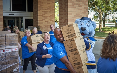 Employees and St. Louis Blue's Louie load diapers to deliver to the St. Louis Area Diaper Bank